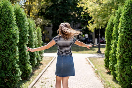 young pretty caucasian woman in casual clothes having fun turning around on trees background in the park