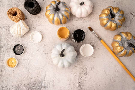 Halloween concept. Halloween DIY crafts. White and gold painted pumpkin on the table with pains top view flat lay