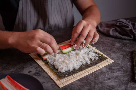 Man in a grey apron cooking homemade sushi rools