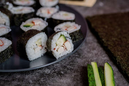 homemade sushi rolls on dark background front view