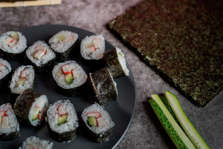 homemade sushi rolls with crab meat and cucumbers at the dark background Reklamní fotografie