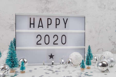white letter lightbox with Happy 2020 surrouded with christmas decorations front view