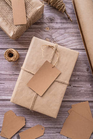 Gift boxes wrapped in craft paper with tags and labels on wooden background top view flat lay