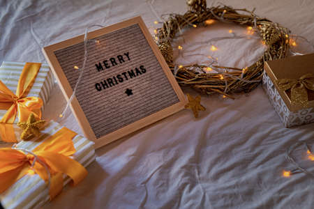 """Christmas and New Year concept. Felt letter board """"Merry Christmas"""" on the bed decorated with golden wreath, lights and gift boxes"""