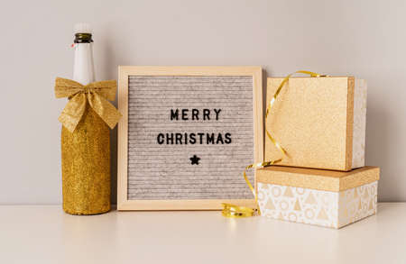 Christmas and New Year concept. Felt letter board Merry Christmas decorated with golden champagne bottle and gift boxes