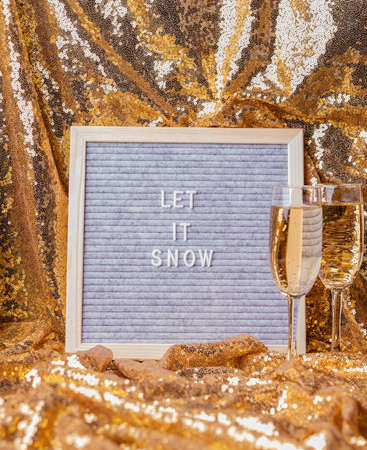 New Year concept. Felt letter board Let It Snow on golden shiny background with champagne glasses