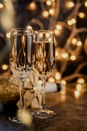 New Year concept. New years eve dark party table with two champagne flute, shiny bottle and christmas lights