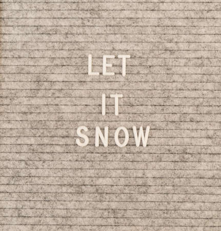New Year concept. The words Let It Snow on the grey felt letter board