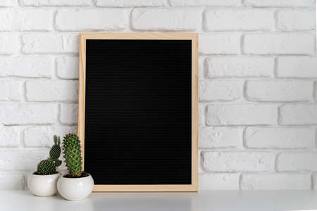 lavagna nera in feltro con piccole piante grasse su sfondo di mattoni bianchi