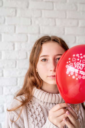 Valentines Day concept. Woman hiding her face behind a red balloon with the words I Love You on white bricks background Banco de Imagens