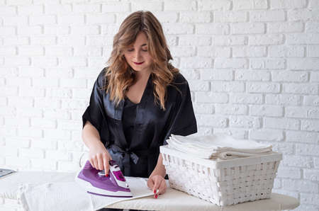 young attractive woman ironing at home with copy space Stock Photo