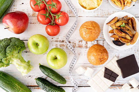 Healthy and unhealthy food concept. Fruit and vegetables vs sweets, burgers and potatoe fries top view flat lay on white rustic background