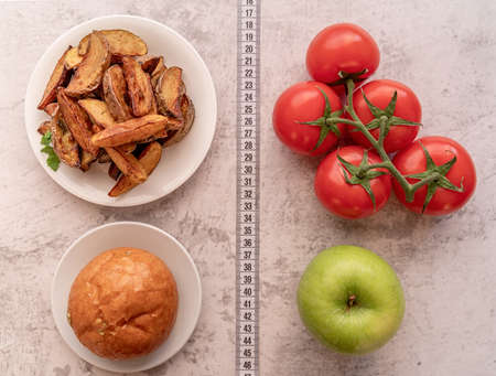 Healthy and unhealthy food concept. Fruit and vegetables vs sweets and potato fries top view flat lay with a measuring tape