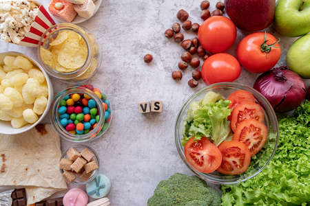 Healthy and unhealthy food concept. Fruit and vegetables vs sweets and potato fries top view flat lay