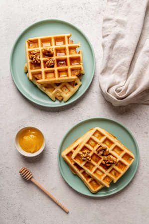 Top view of waffles with walnuts and honey. Flat lay