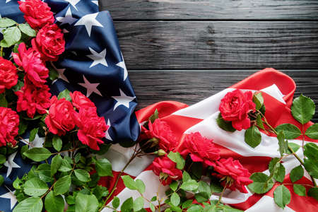 Independence Day USA concept. Memorial Day. Red roses over the USA flag on dark wooden background top view flat lay with copy space Banco de Imagens
