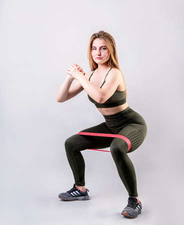 Young athletic woman doing squats using rubber resistance band isolated on gray background