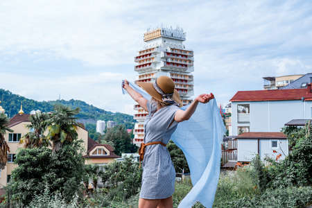 young woman in summer dress dancing and turning around holding a scarf on summer city background