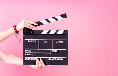 A movie production clapper board. Female hands holding a clapper board isolated on pink