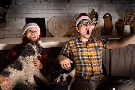 Young couple watching movies at home at christmas pointing to the screen