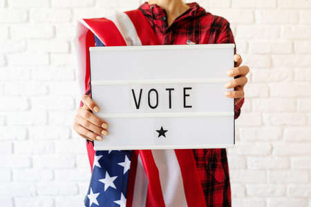 Black letter board with the text your vote matters with American flag on white marble background
