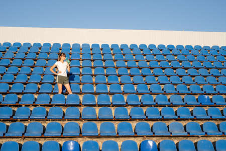 Sports and fitness. Teenager girl getting ready to run at stadium track