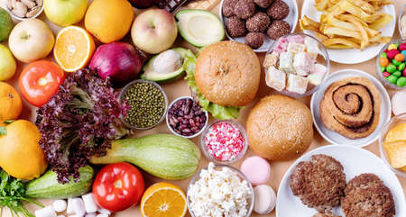 Fruit and vegetables vs sweets and fast food top view flat lay on orange background