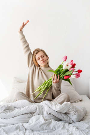 Happy smiling woman sitting on the bed wearing pajamas, with pleasure enjoying flowers, chatting using laptop