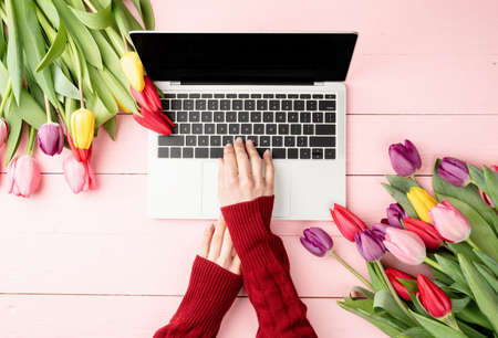 Easter and spring concept. Top view of laptop computer, colorful tulips and Easter eggs on pink wooden background
