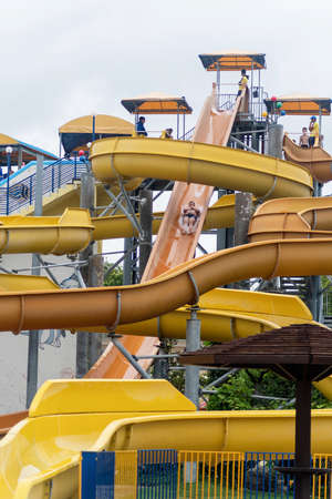 Summer vacation. Colorful plastic slides in aquapark. Water park and splashes Stock Photo