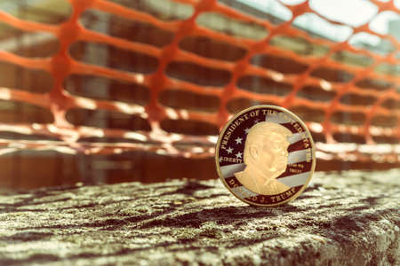 Trump coin with construction works in the background Stok Fotoğraf