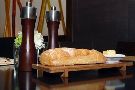 ciabatta: Restaurant table setting: salt and pepper shakers next to ciabatta bread Stock Photo