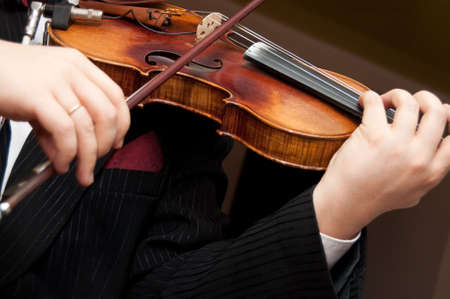 violist: No Model here. Closeup of musician playing the violin during a symphony