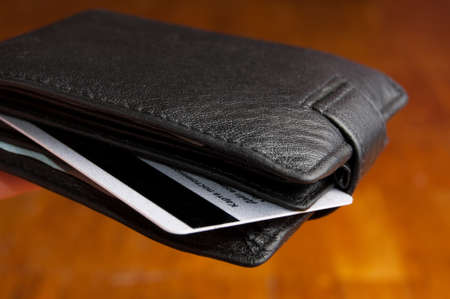 boodle: Black leather wallet on a Brown background