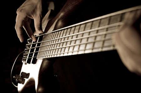 hands of a boy playing bass guitar photo