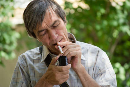 Man lighting a cigarette on the nature. photo