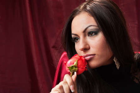The beautiful woman with a rose on red background photo