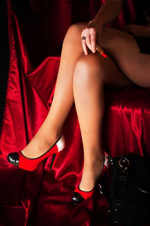 beautiful sexy legs with rad shoes on red background photo