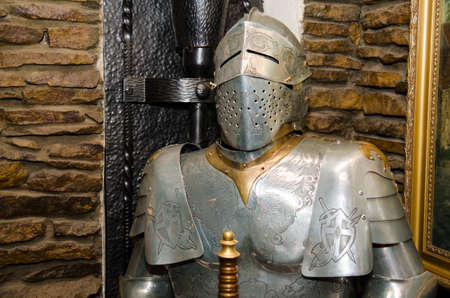 Ancient metal armor with iron detail near the wall of castle photo