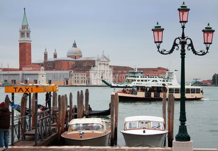 Taxi boats, gondola, vaporetto and ferry boat in front of San Giogio Maggiore Island, Venice, Italy