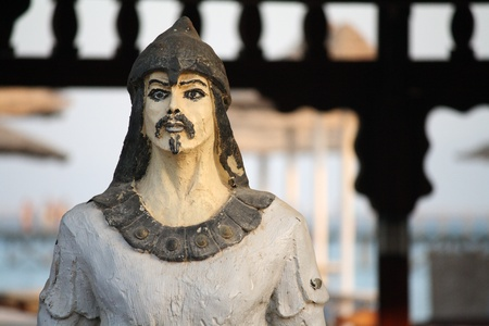 An ancient warrior statue in front of a gate