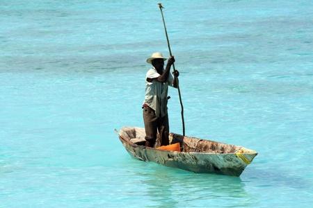zanzibar: Zanzibar, Tanzania - 18 oktober 2010: Een visser vaart op de voorkant van Nungwi, een van de meest charmante plekken in Zanzibar, met helder water en witte zandstranden. Redactioneel