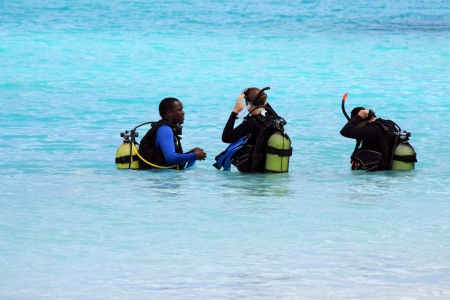 Zanzibar, Tanzania - October 18, 2010: A professional diver teaches two women how to dive in the crystal waters of Nungwi.