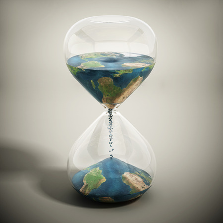 Melting world concept with earth textured sand pouring inside the hourglass.