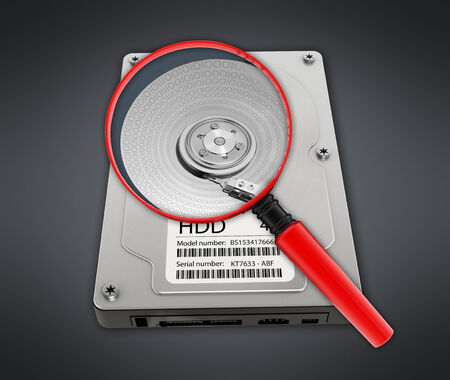 hard disk drive: Magnifying glass on hard disk drive showing binary code.