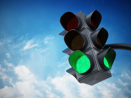 Green traffic light against blue sky. Stock Photo
