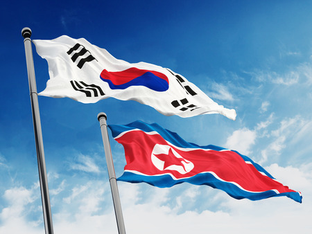 north korea: South and North Korea flags against blue sky background.