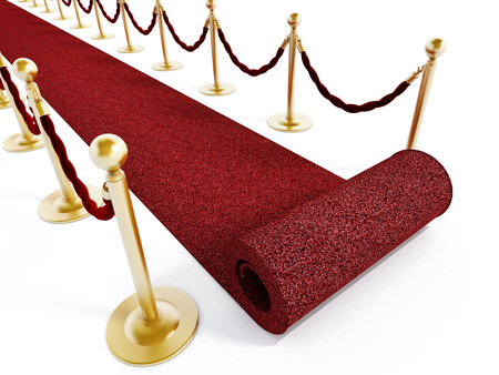 Rolled red carpet and velvet ropes isolated on white background photo