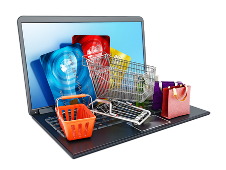 Shopping cart, credit cards and bags standing on laptop computer isolated on white background. 3D illustration.
