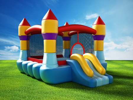 Bounce house standing on green grass. 3D illustration. Stock Photo